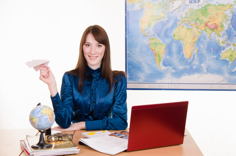 Young beautiful employee in the office of the travel agency