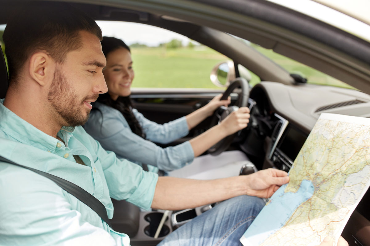 happy man and woman with road map driving in car